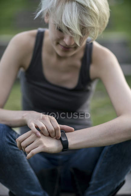 Smiling young woman checking her smartwatch — Stock Photo