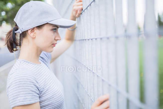 Femme portant la casquette de baseball à la recherche par le biais de clôture — Photo de stock