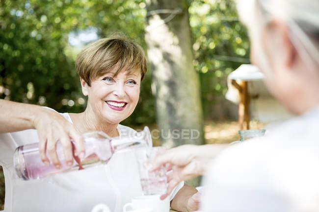 Усміхаючись старший жінка розливу води в друзі скло — стокове фото