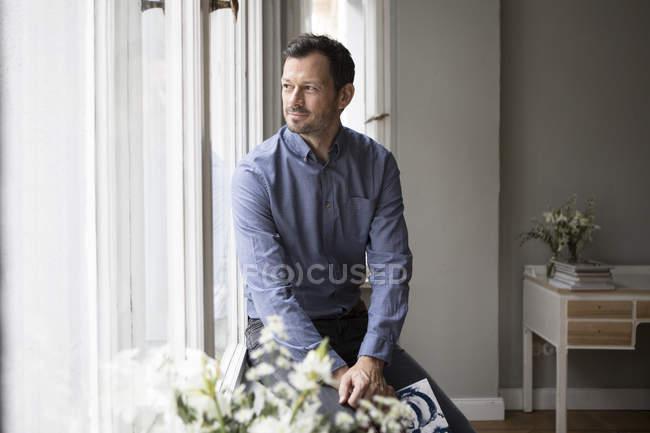Улыбающийся человек, сидя на подоконнике смотрит что-то — стоковое фото