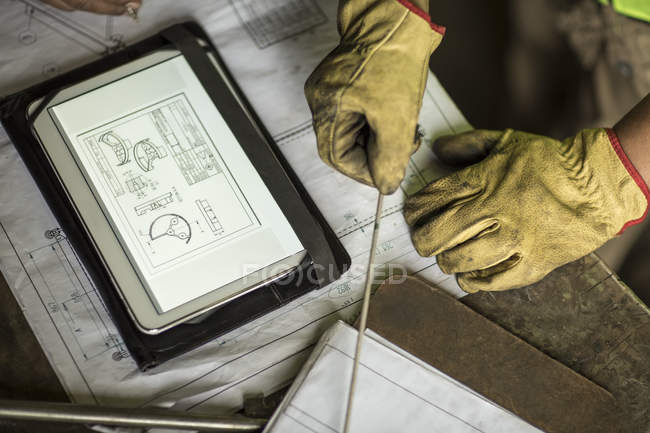 Man in construction company working with blueprint on digital tablet — Stock Photo
