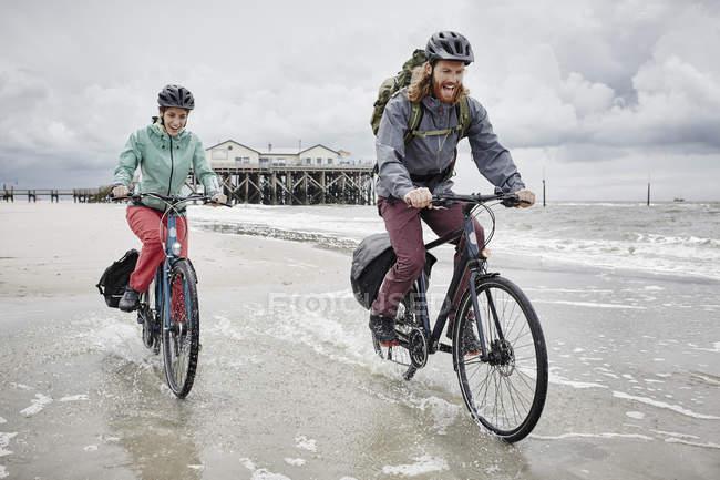 Casal feliz andar de bicicleta na praia — Fotografia de Stock