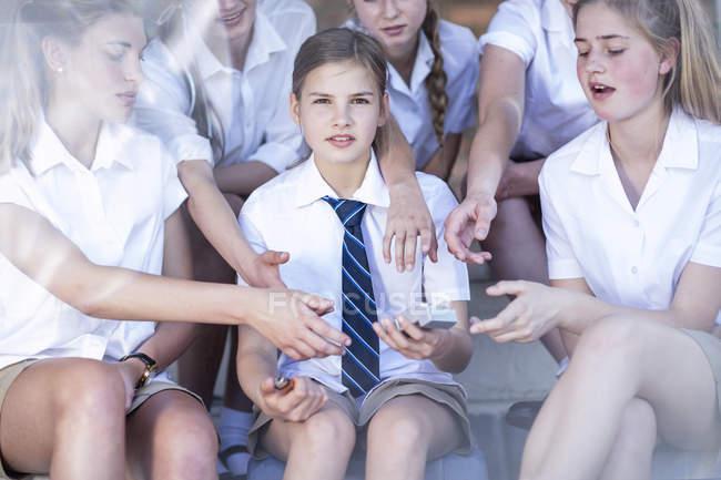 Estudiantes de secundaria que ofrecen cigarrillos a una chica - foto de stock