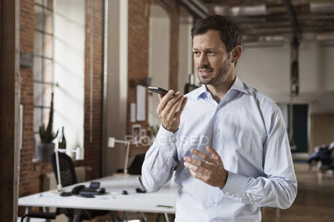 Businessman using cell phone in office — Stock Photo