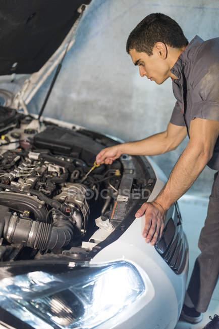 Young mechanic repairing car in a garage — Stock Photo