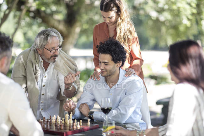 Cape Town, South Africa, Male seated with family playing chess games outside together — Stock Photo