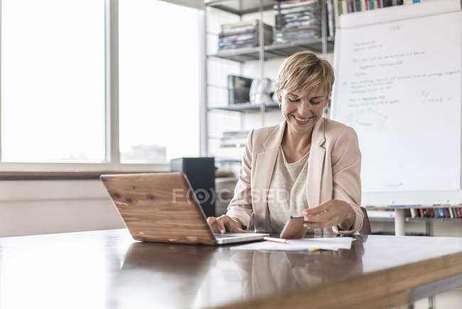 Smiling businesswoman with cell phone and laptop in modern conference room — Stock Photo