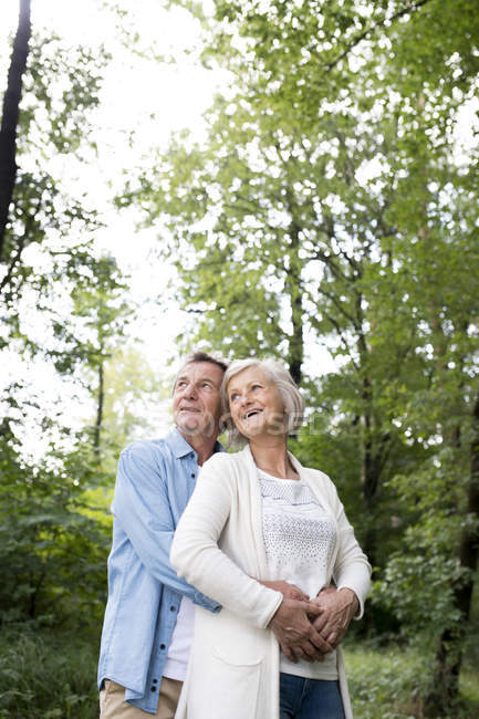 Active cute senior couple hugging together in park — Stock Photo