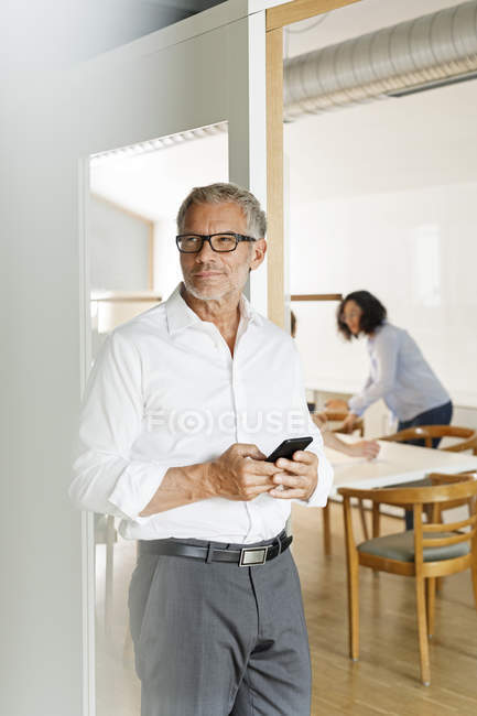 Cuacaisan businessman with cell phone in office — Stock Photo