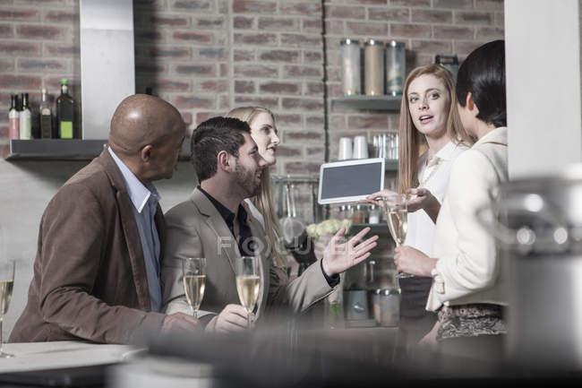 Жінка показ планшетний друзям з шампанським окуляри на дому — стокове фото