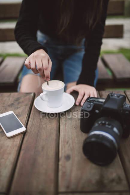 Женщина в кафе на открытом воздухе помешивает кофе — стоковое фото