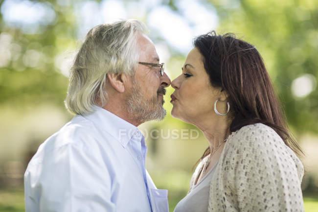 Старший мужчина целует старшую женщину в саду — стоковое фото