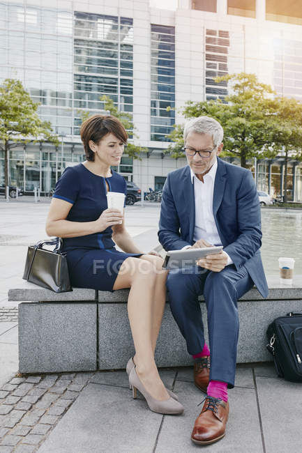Businessman and businesswoman with digital tablet outdoors — Stock Photo