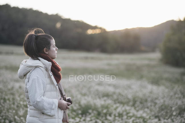 Pensive woman with camera in nature — Stock Photo