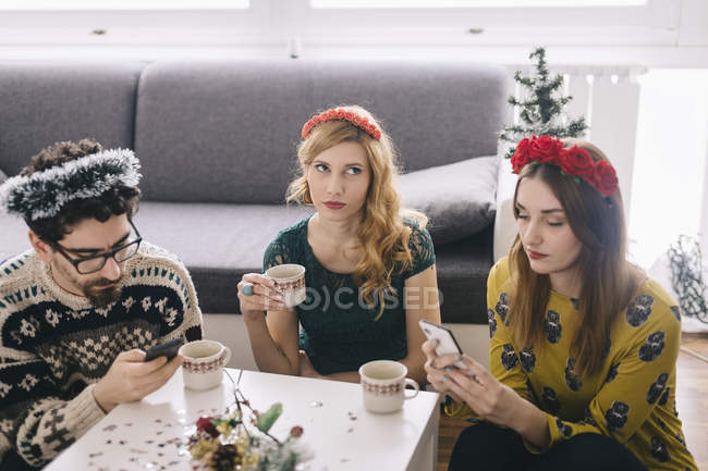 Annoyed young woman sitting between her friends looking at her smartphones — Stock Photo