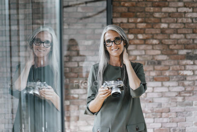 Portrait of smiling woman with long grey hair holding camera — Stock Photo
