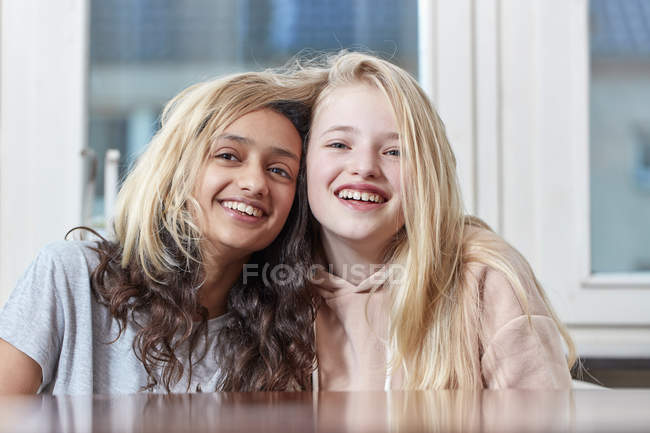 Portrait of two happy girls playing with hair — Stock Photo