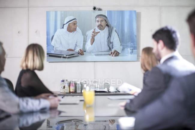Des hommes d'affaires en vidéoconférence avec des clients du Moyen-Orient — Photo de stock