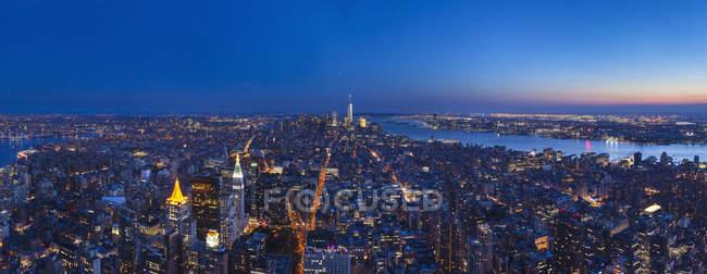 Estados Unidos, Nueva York, Manhattan, panorama del distrito financiero iluminado al anochecer, antena vista - foto de stock
