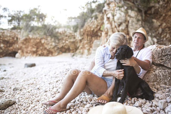 Active cute senior couple relaxing together on beach with dog — Stock Photo
