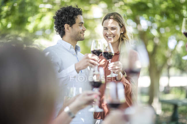 Couple de lever un toast avec vin à l'extérieur de jardin — Photo de stock