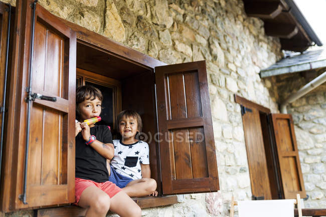 Two little brothers relaxing on window sill of holiday home — Stock Photo
