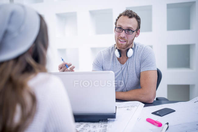Людина з ноутбуком, маючи зустріч з жінкою в офісі — стокове фото