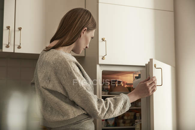 Woman looking into fridge standing  in kitchen — Stock Photo