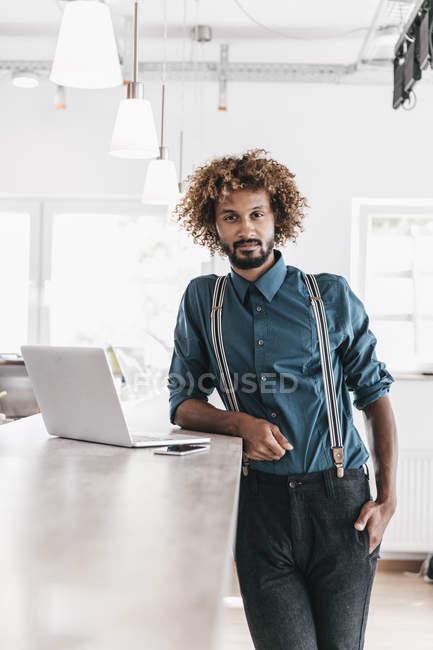 Молодой человек опирается на стол с ноутбуком в современном офисе — стоковое фото