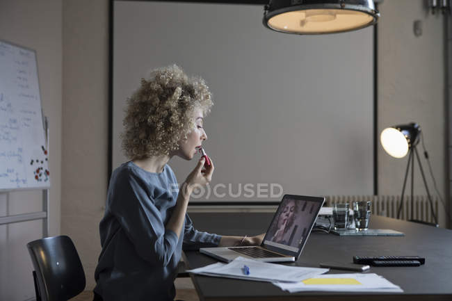 Woman in office applying make-up and using laptop monitor as mirror — Stock Photo