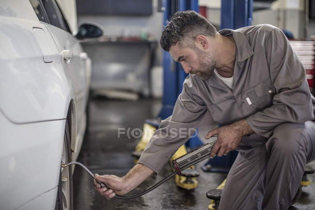 Car mechanic in a workshop filling up tire — Stock Photo