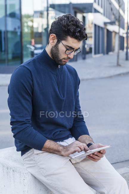 Young man sitting on bollard and using mini tablet — Stock Photo