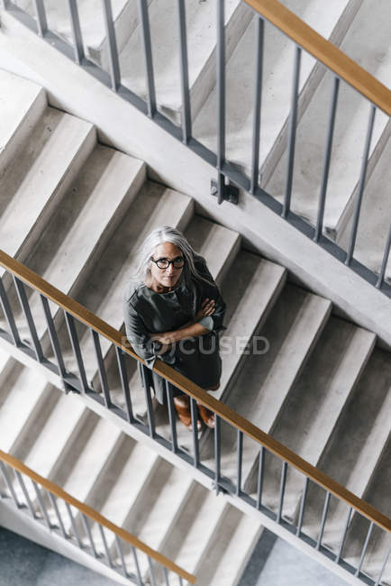 Woman with long grey hair standing in staircase — Stock Photo