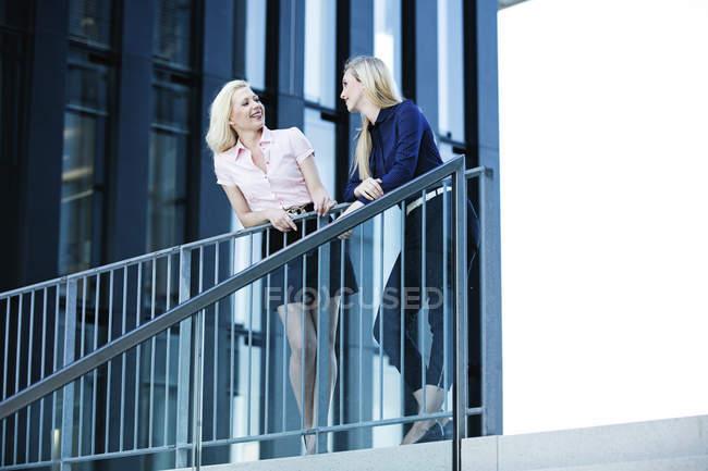 Due donne d'affari che parlano accanto alle scale dell'edificio — Foto stock