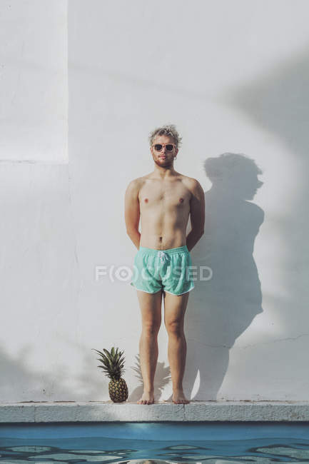 Young man standing at poolside next to pineapple — Stock Photo