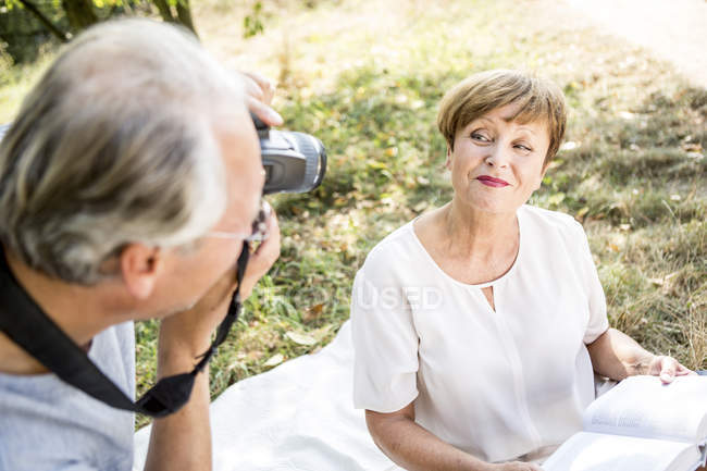 Senior man photographing woman with book sitting outdoors — Stock Photo