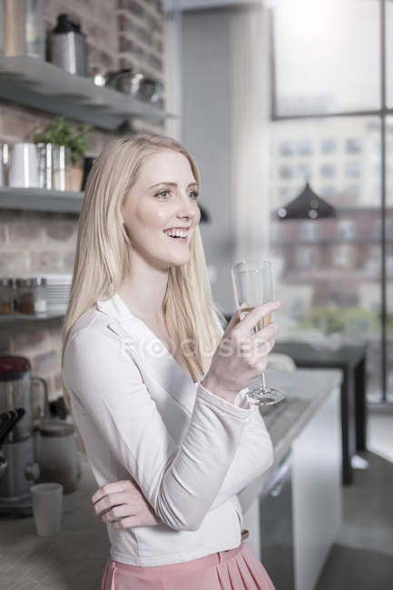 Усміхаючись молодої жінки п'ють шампанське відкритого планування кухні — стокове фото