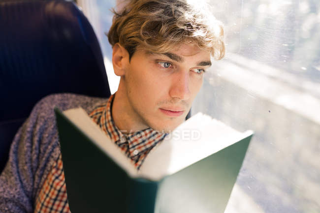 Pensive young man with book sitting in a train looking through window — Stock Photo