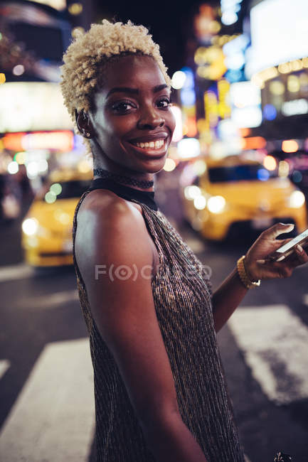 Portrait of happy young woman with cellphone on Times Square at nighttime, USA, New York City — Stock Photo