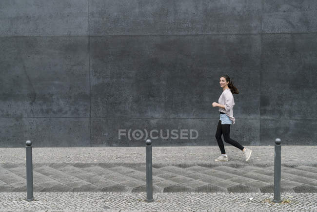 Молодая женщина бежит по городу — стоковое фото
