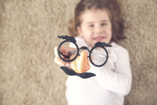 Little girl lying on the carpet holding funny glasses with plastic nose, close-up — Stock Photo
