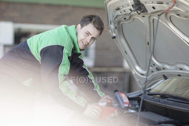 Male petrol attendant pours motor oil into car at fuel station — Stock Photo