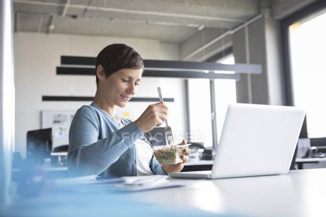 Деловая женщина обедает за столом в офисе — стоковое фото