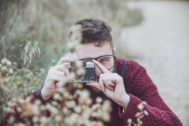 Бородатый мужчина фотографирует цветы на винтажную камеру — стоковое фото