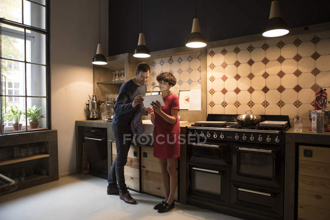 Couple standing in the kitchen and using digital tablet — Stock Photo