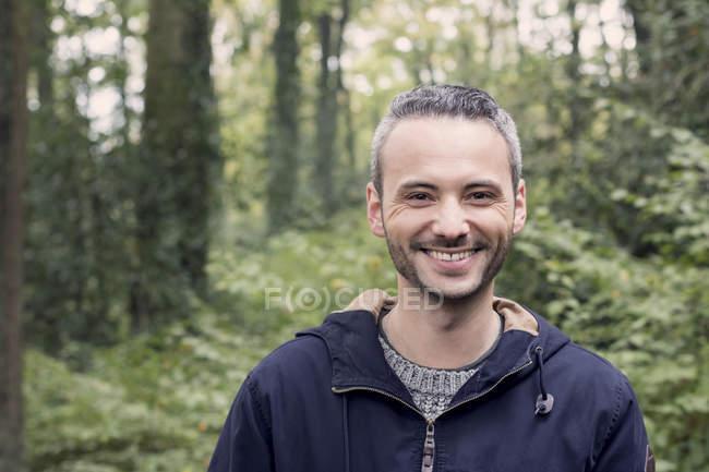 Retrato de homem sorridente em pé na floresta — Fotografia de Stock