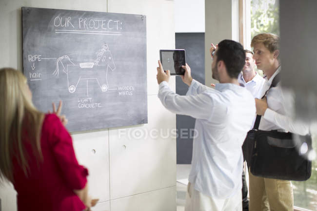 Молодые люди, совместной работы в современном офисе, человек принимает фото презентации с таблеткой — стоковое фото