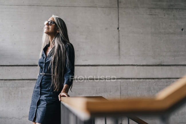 Smiling woman with long grey hair in staircase — Stock Photo