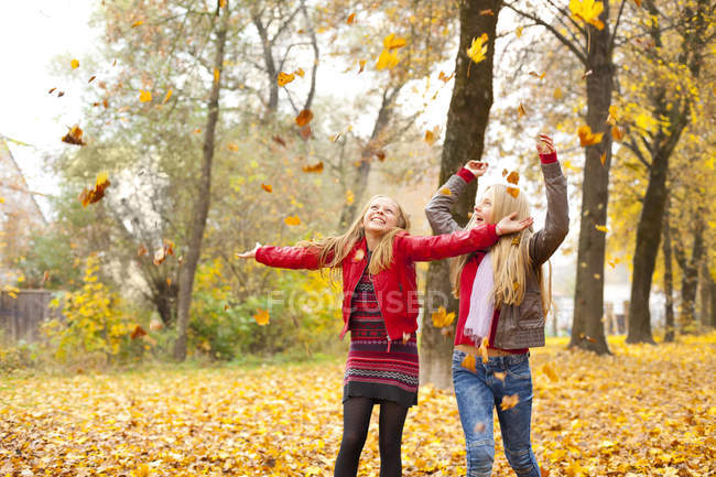 Two happy girls throwing autumn leaves in the air — Stock Photo