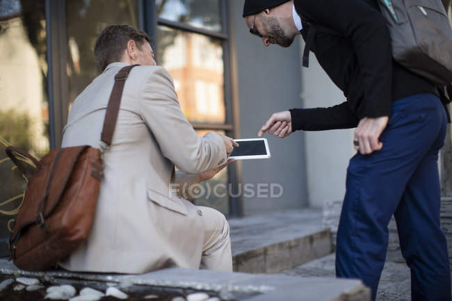 Two caucasian businessmen with tablet outdoors — Stock Photo